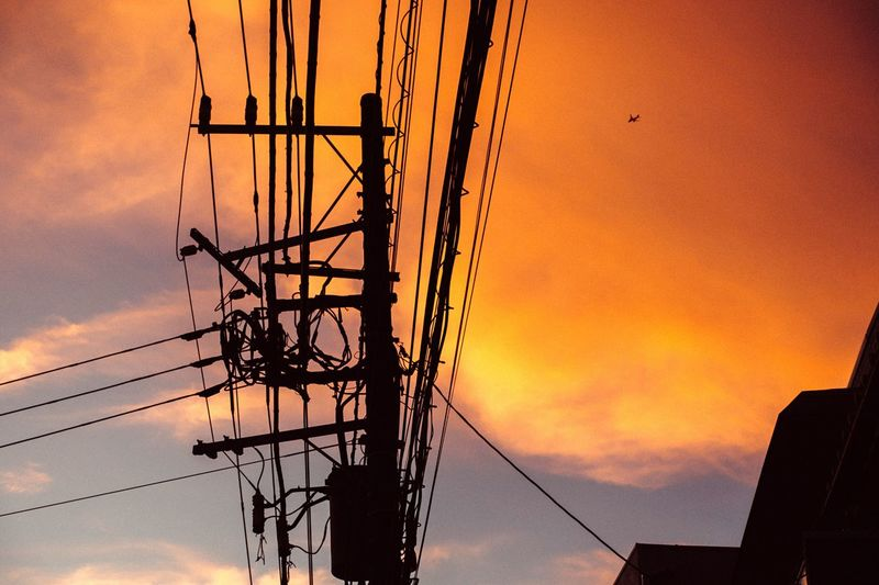 Low angle view of silhouette electric pole against orange sky