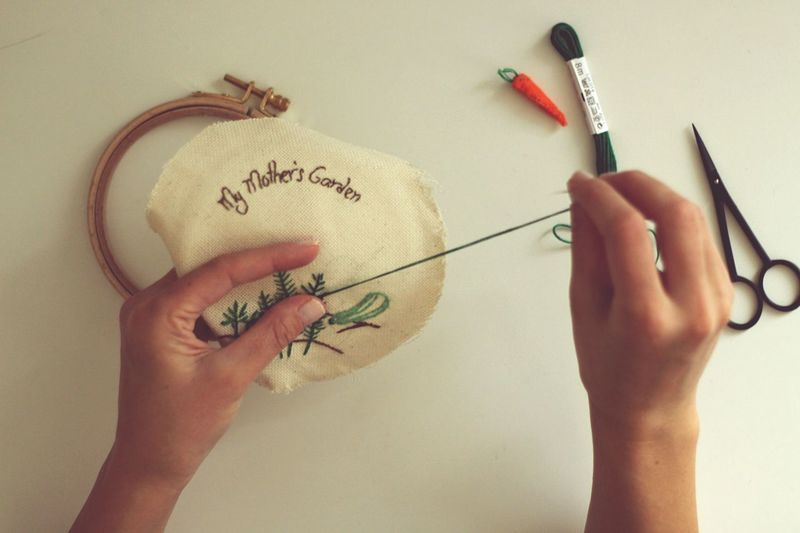 Cropped image of craftsperson doing embroidery on cloth over white background