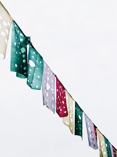 Low angle view of flags hanging against white wall