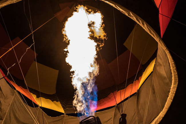 "An ignited propane burner keeps an hot air balloon inflated during a ""glow"", a display at night where the balloon remains tethered to the ground and the burner illuminates the envelope. Hot Air Balloon Low Angle View Night No People Outdoors Propane Burner Winter"