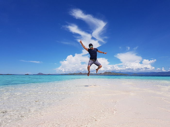 Full length of mid adult man jumping at beach against blue sky during sunny day