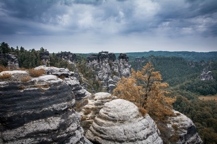 Rock formations against cloudy sky at saxon switzerland