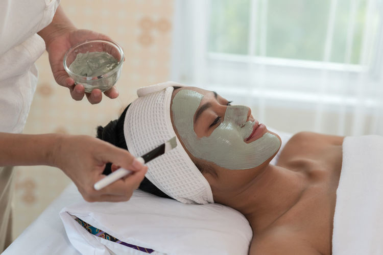 Midsection of beautician applying facial mask on smiling woman face at spa