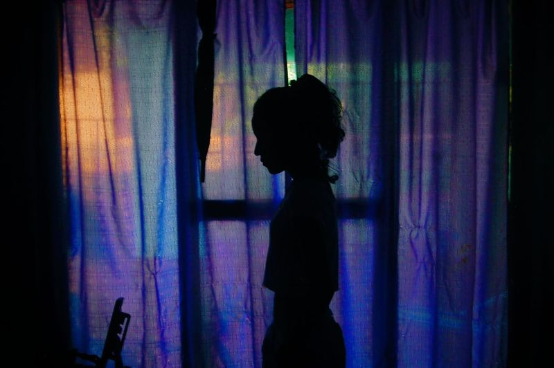 Silhouette girl standing by curtain at home