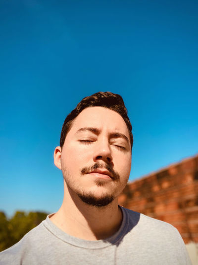 Portrait of young man against clear blue sky