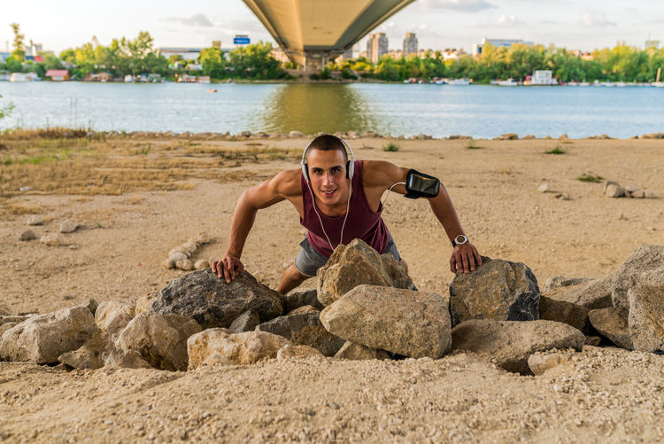 Portrait of young man exercising on rocks