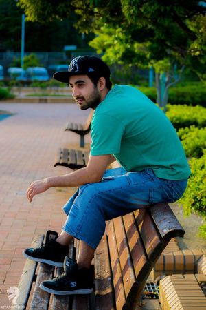 Baseball Cap Cap Casual Clothing Day Focus On Foreground Full Length Leisure Activity Lifestyles Nature One Person Outdoors People Real People Side View Sitting Tree Young Adult