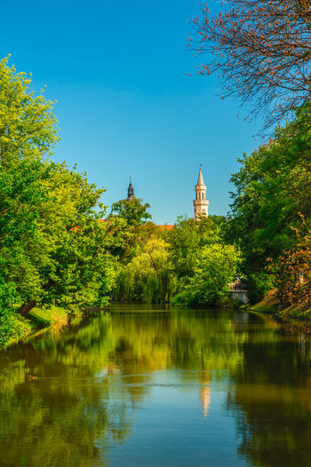 Two towers rising above the river Tree Sky Water Plant Religion Reflection Architecture Place Of Worship Lake Belief Built Structure Nature Spirituality Building Building Exterior No People Growth Green Color Waterfront Outdoors Spire  Opole Opole Poland