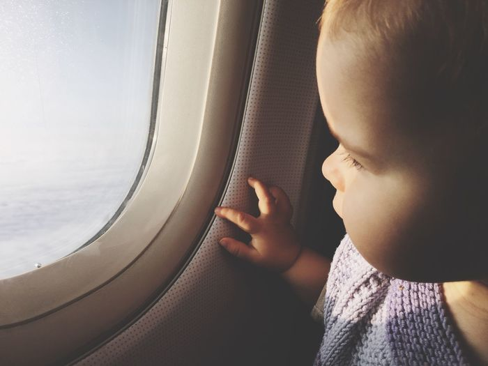 Midsection of boy looking through airplane window