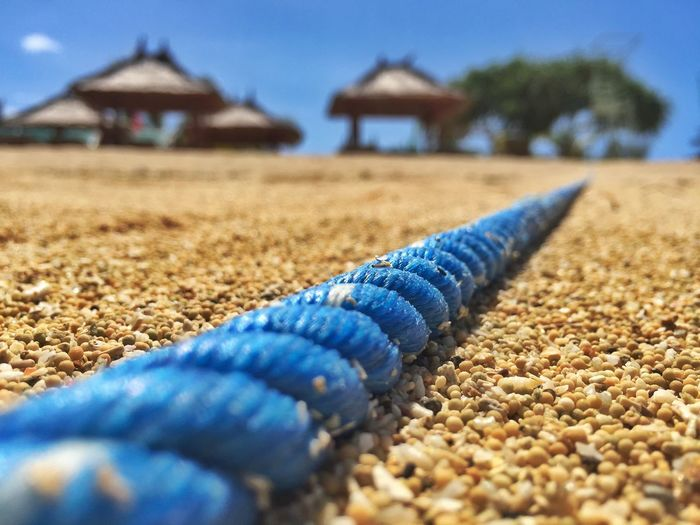 Close-up of blue rope at beach by huts against sky