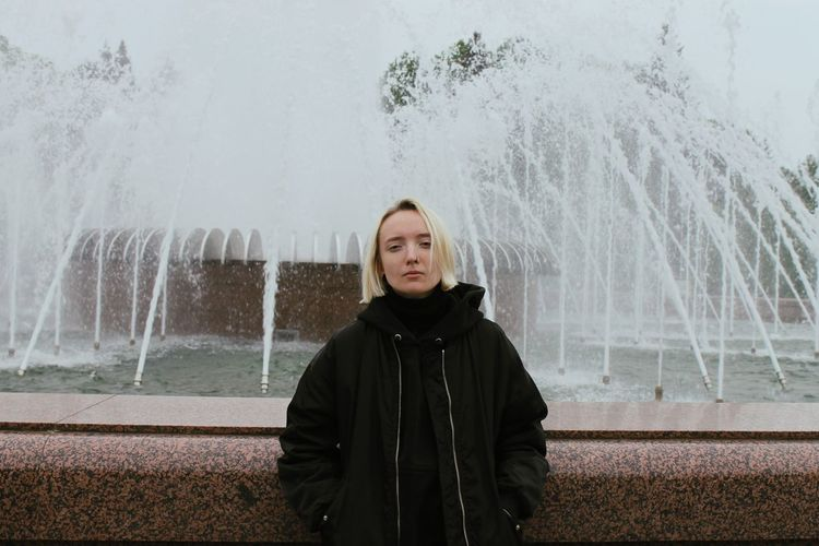 Portrait of a girl against the background of a fountain in the style of the 90s