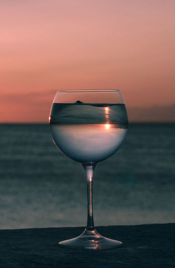 Wineglass on table against sea during sunset