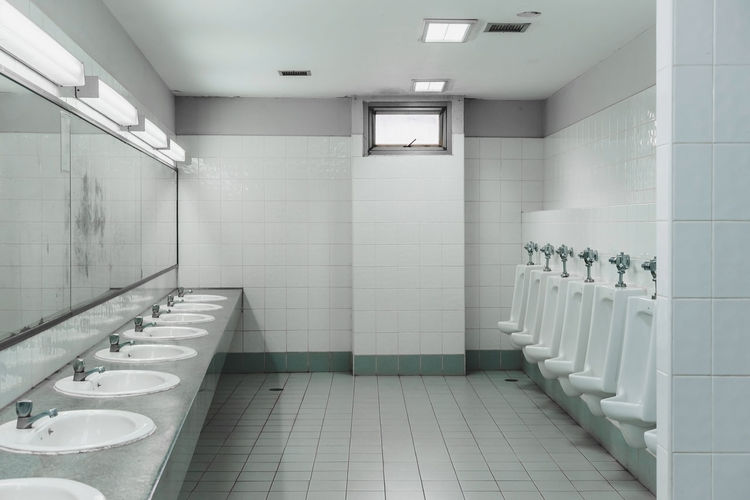 Urinals and sinks in empty public restroom