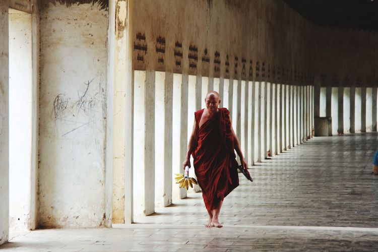 Full length of monk walking in corridor
