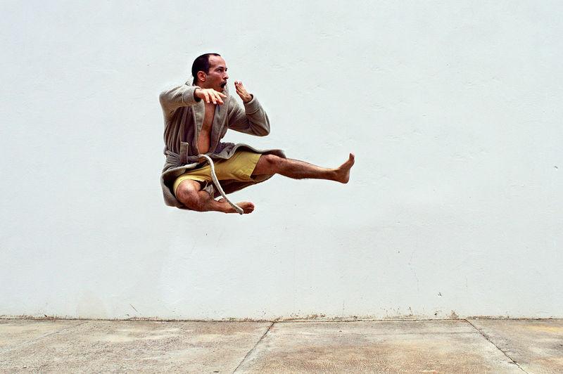 Young man jumping while yawning