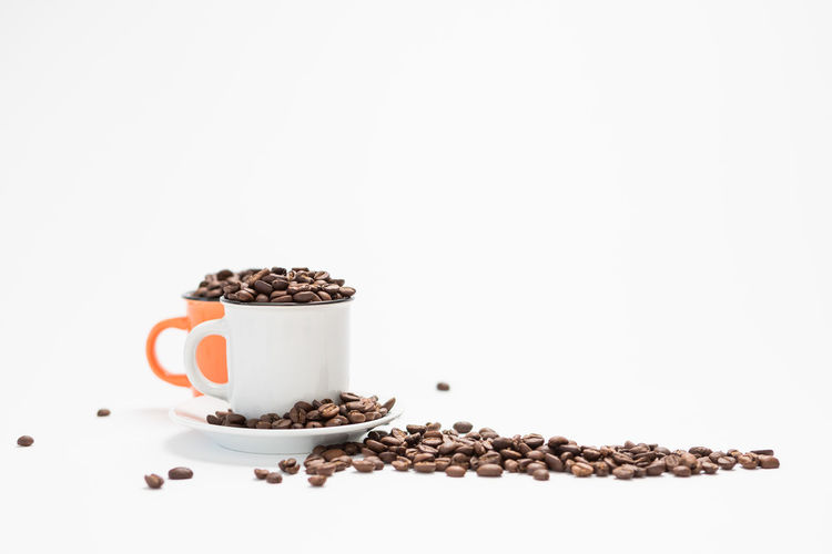 Coffee Cups Filled with Coffee Beans on a White Background Concept with Copy Space White Background Food And Drink Studio Shot Food Copy Space Indoors  Roasted Coffee Bean Still Life Freshness No People Coffee - Drink Seed Large Group Of Objects Brown Coffee Spice Cup Mug Wellbeing