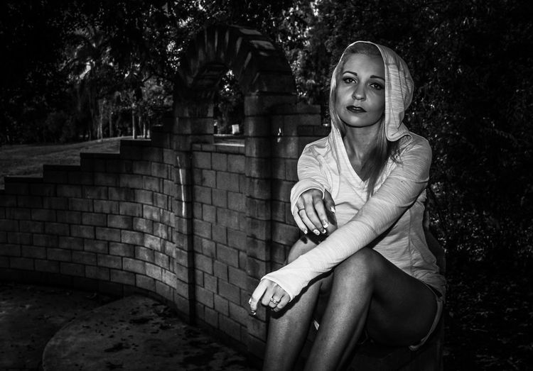 Portrait of woman sitting by retaining wall at park