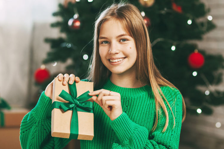 Portrait of smiling young woman with christmas tree