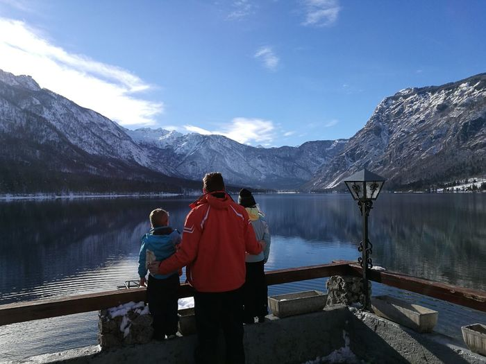 Rear view of father with children looking at lake and mountains against sky