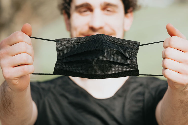 Close-up portrait of man holding mask