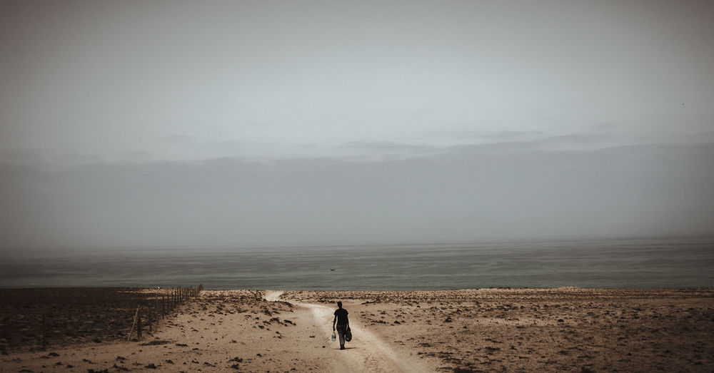 Rear view of man walking on landscape by seascape against sky