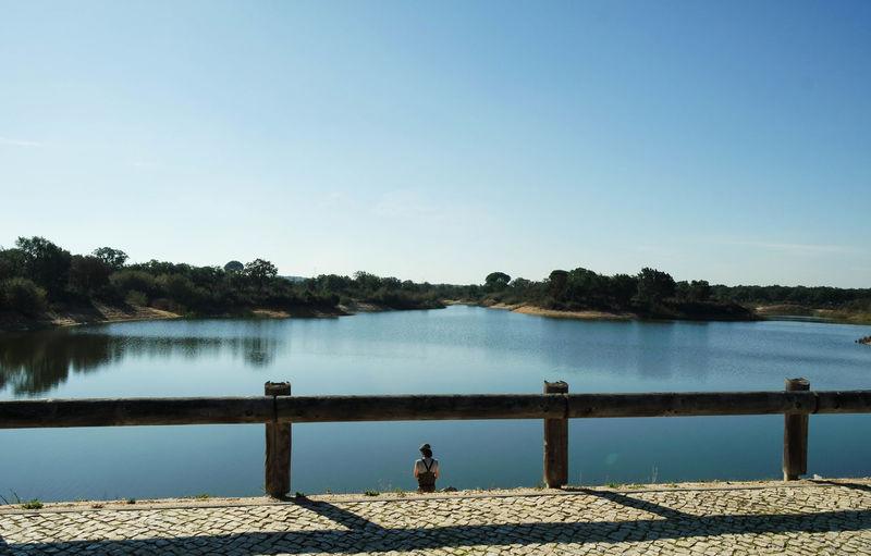 Rear view of woman by calm lake