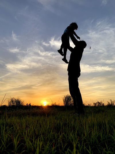 Silhouette Father Carrying Son Against Sky During Sunset. Man Father Child Son Family Dad Silhouette People Kid Boy Carrying Carry Lift Happy Parent Together Lifestyle Fun Young Holiday Sunset Vacation Outdoor Male Daddy Healthy Leisure Summer Joy Love Day Freedom person Nature Travel Active Couple Sunrise Little Childhood