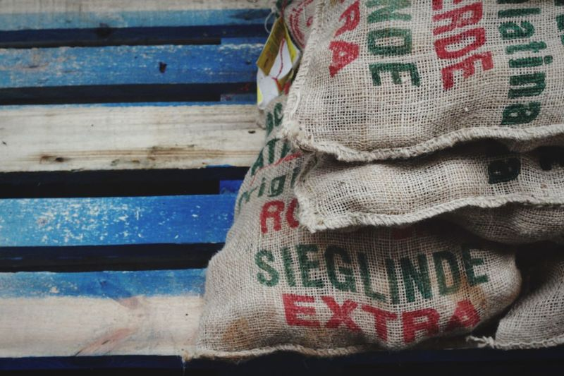 Bags of coffee beans ready to go in burlap sacks. Italy Color Blue Wood Coffee Shipping  Agriculture Textile No People Close-up Text Clothing Sack Pattern Textured  Detail Torn Still Life