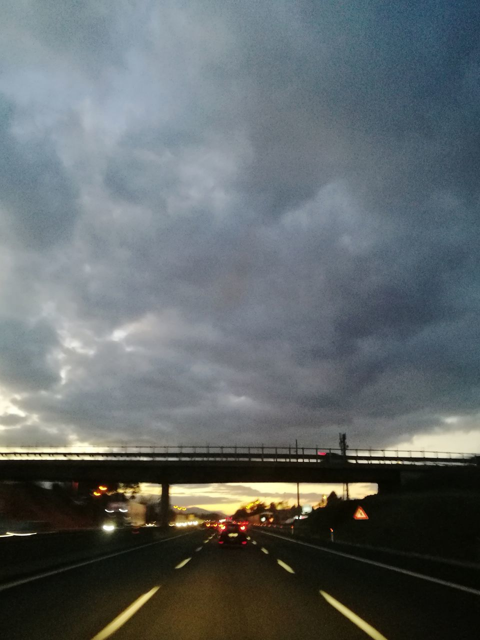 cloud - sky, transportation, sky, road, motor vehicle, mode of transportation, car, sign, no people, land vehicle, the way forward, highway, nature, street, direction, dusk, illuminated, symbol, traffic, bridge - man made structure, outdoors, multiple lane highway, dividing line
