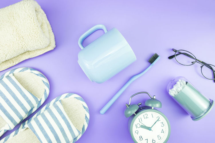 High Angle View Of Personal Accessories On Purple Background