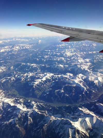 Aerial view of airplane flying over snowcapped landscape against sky