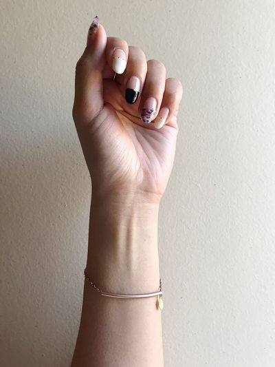 Cropped Image Of Hand Wearing Bracelet Against Wall
