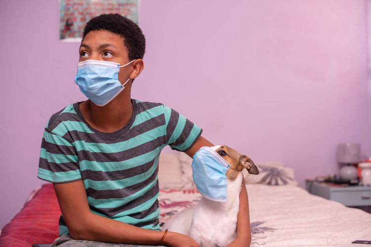 Portrait of young boy and his pet wearing protective mask