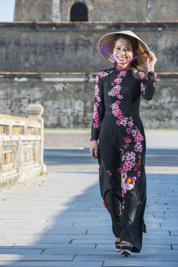 Full length portrait of woman standing against built structure