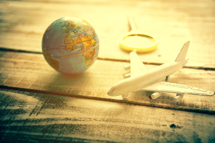 Close-up of airplane toy and globe on table