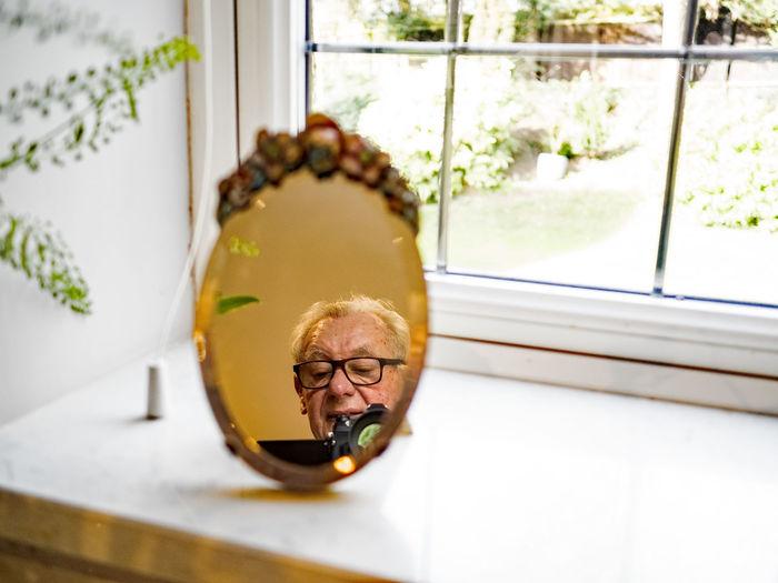Portrait of man wearing mask against window