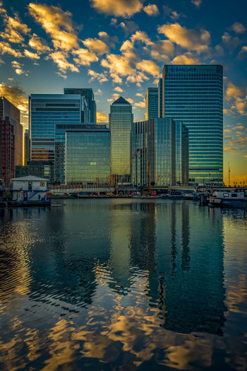 Modern buildings by river against sky during sunset in city
