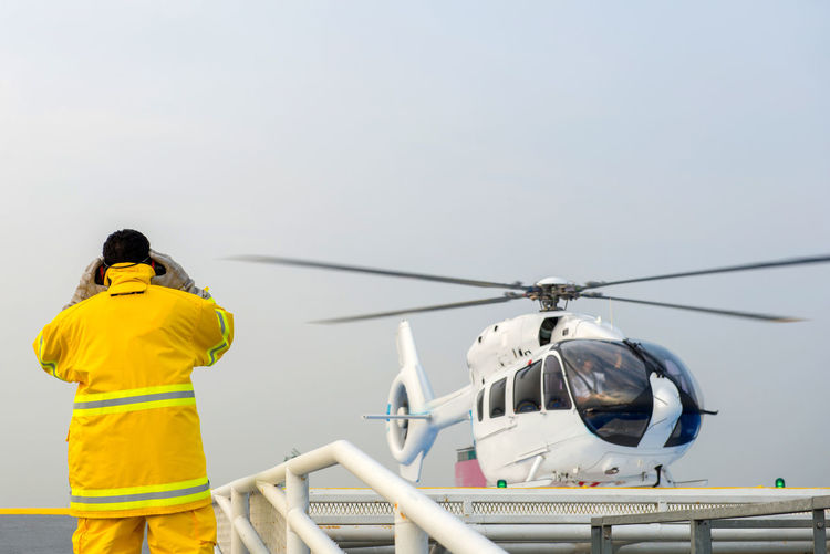 Rear View Of Worker Standing Against Helicopter