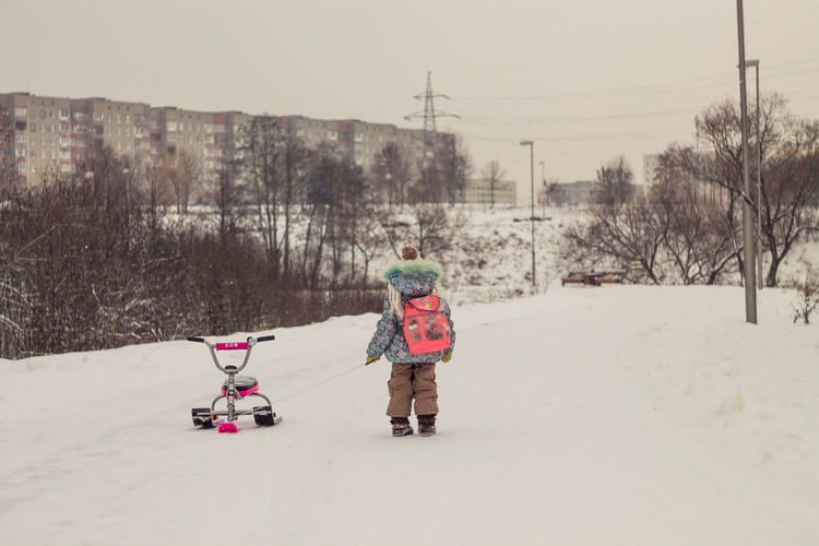 Winter Real People Cold Temperature Warm Clothing Snow Child Childhood Rear View Clothing Sky Nature One Person Lifestyles Transportation Walking Females Outdoors
