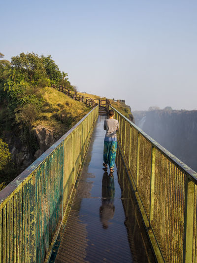 Woman Standing On Footbridge Against Clear Sky At Victoria Falls, Zambia