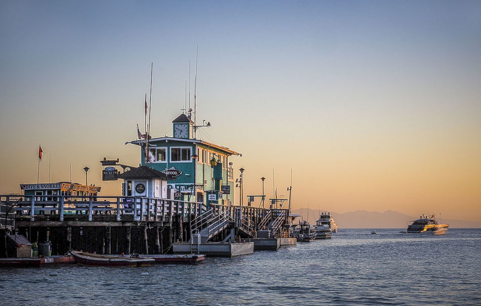 Beauty In Nature Boat Boats Catalina Island  First Light Gold Sky Green Pier Island Nautical Vessel No People Pier Sunkissed Boat Sunlit Boat Sunrise Water Wharf Wharf At Sun