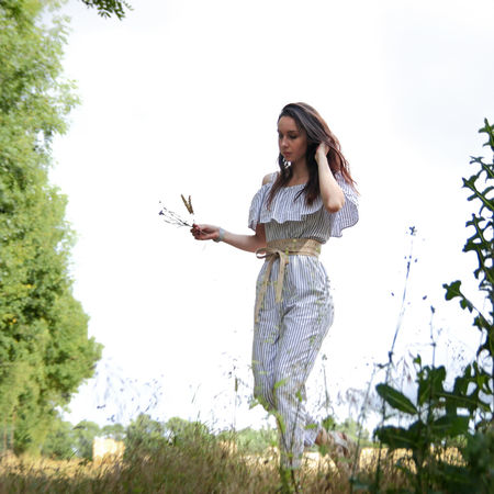 Beautiful Woman Beauty In Nature Casual Clothing Day Field Full Length Grass Happiness Holding Leisure Activity Lifestyles Low Angle View Nature One Person Outdoors Real People Sky Smiling Standing Tree Women Young Adult Young Women