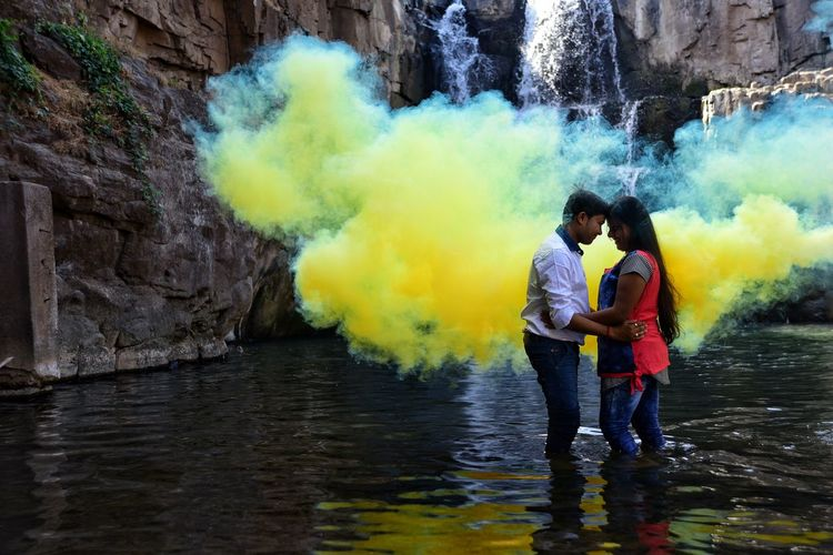 Young Couple Standing Against Waterfall In River