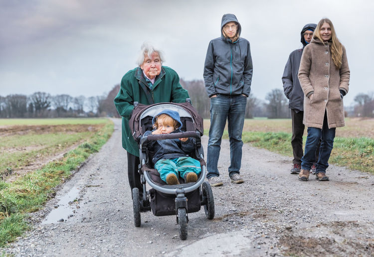 Family with baby walking on dirt road against sky during winter