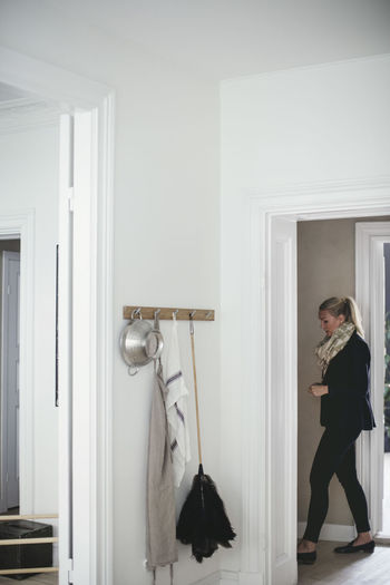 Woman standing by door at home