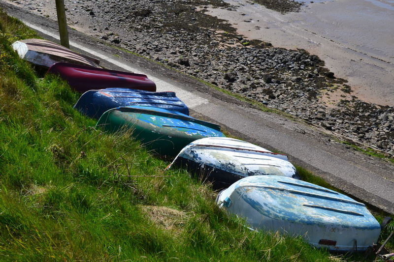 A Row of Upturned Painted Boats on the Riverbank Boat Hull Colored Boats Grass Grassy Bank Line Of Boats Nautical Vessel No People Outdoors Riverbank Rowing Boat Upside Down Upturned Upturned Boat Water