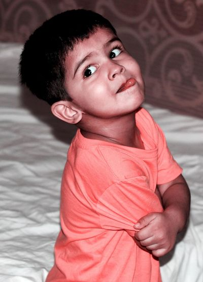 Close-up of boy sticking out tongue while standing by bed at home