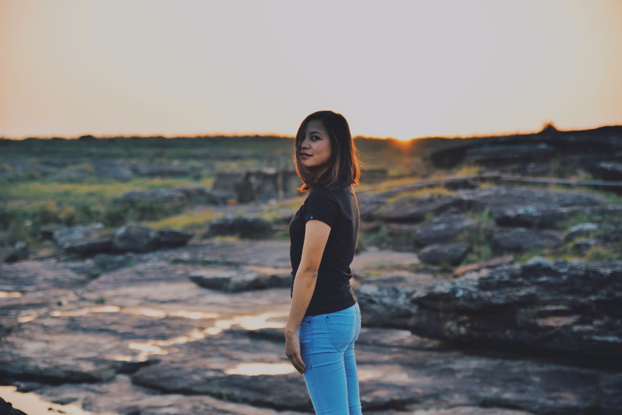 one person, standing, sky, young adult, real people, lifestyles, leisure activity, sunset, young women, looking at camera, women, nature, focus on foreground, adult, casual clothing, three quarter length, portrait, land, side view, outdoors, beautiful woman, hairstyle