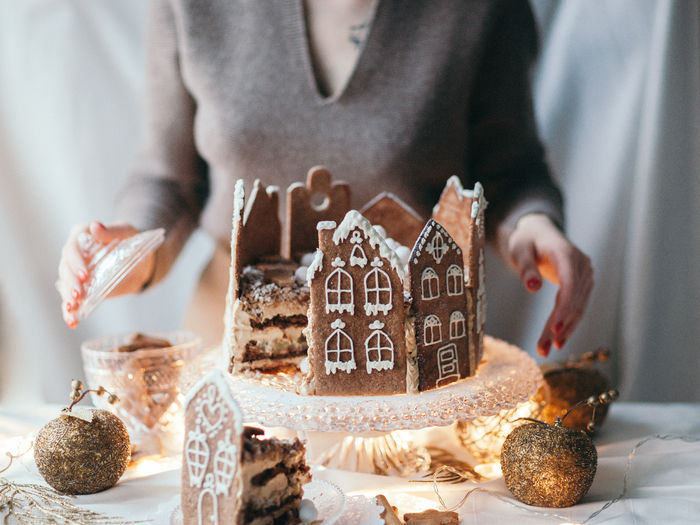 One Person Indoors  Real People Celebration Holding Christmas Decoration Lifestyles Food Human Hand Focus On Foreground Hand Table Food And Drink Front View Holiday Christmas Decoration Christmas Ornament Cake Serving Gingerbread Gingerbread House Homemade Cake