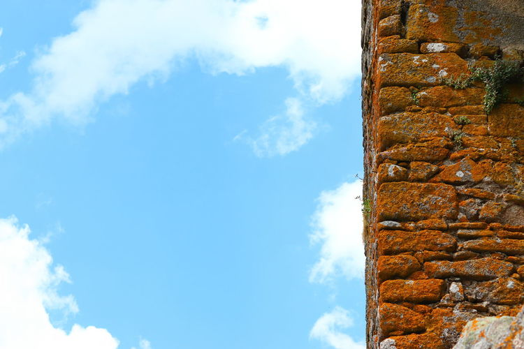 Low angle view of wall and building against sky